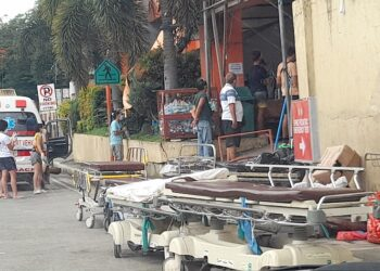 """At least four stretchers are parked on the street outside the emergency section of the Southern Philippines Medical Center in Davao City on Sunday morning, 5 September 2021. There is no space for stretchers inside the emergency room packed with patients seeking admission in the state-run hospital which has been receiving an """"unusually high volume of patients seeking admission for COVID-19."""" From the roadside, one could see a health worker in Personal Protective Equipment performing a cardiopulmonary resuscitation on a patient at the entrance at around 9:15 a.m. MindaNews photo by CAROLYN O. ARGUILLAS"""